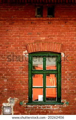 Red brick wall with old green window - stock photo