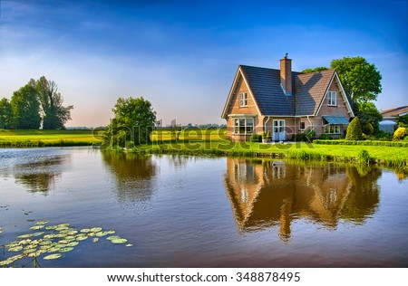 Red bricks house in countryside near the lake with mirror reflection in water, Amsterdam, Holland, Netherlands, HDR - stock photo