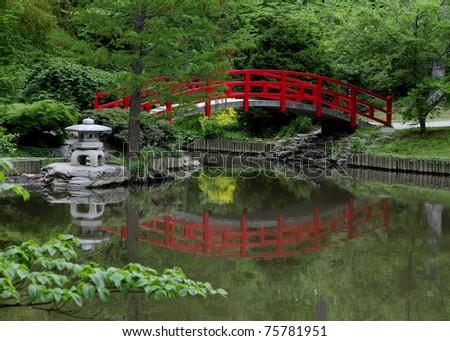 Red Bridge In Japanese Style Garden On Gray Day
