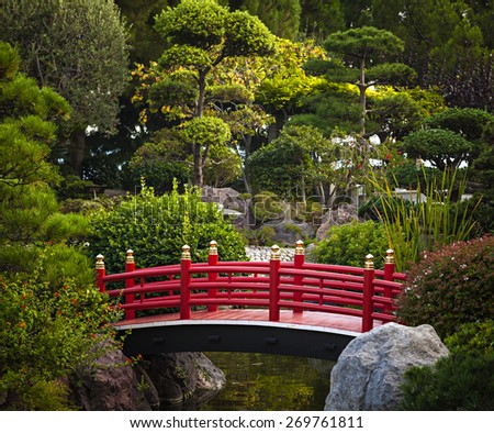 Red bridge over pond in Japanese garden. Monte Carlo, Monaco. - stock photo
