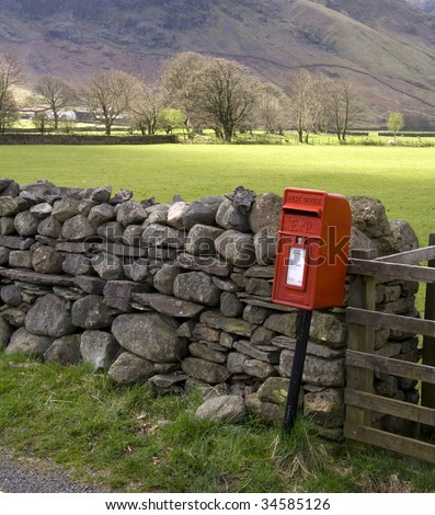 Red British post box by a dry stone wall in the Lake District
