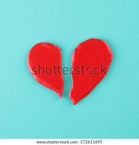 red broken heart on a wooden texture - stock photo