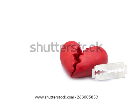 Red broken heart shape made by play dough stab by razor isolate on white background. concept of broken relationship. - stock photo