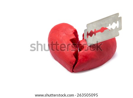 Red broken heart shape made by play dough stab by razor isolated on white background. concept of broken relationship. - stock photo