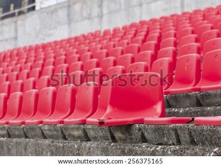 Red broken seats on open-air stands on football stadium - stock photo