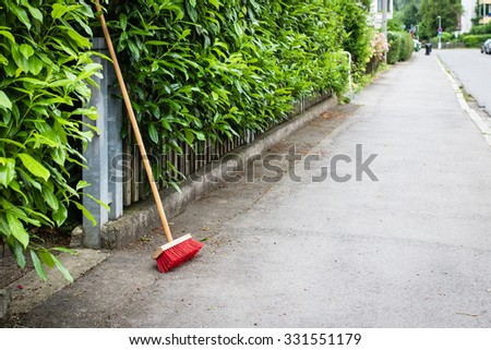 red broom on clean street in little german town, selective focus - stock photo