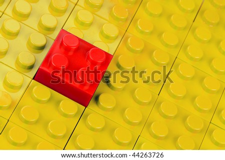 Red building block in a field of yellow ones - stock photo