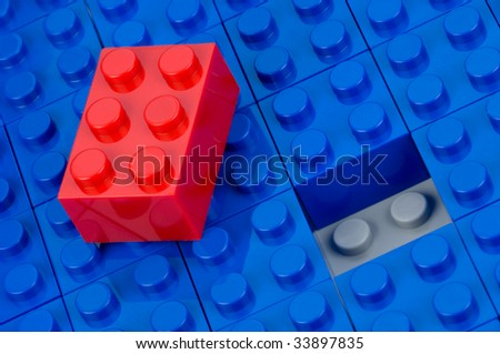 Red building block, unfitted to an field of blue one