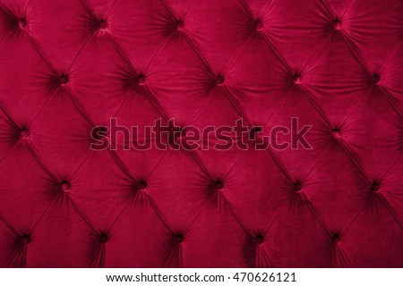 Red burgundy velvet capitone textile background, retro style checkered soft tufted fabric furniture diamond pattern decoration with buttons, close up
