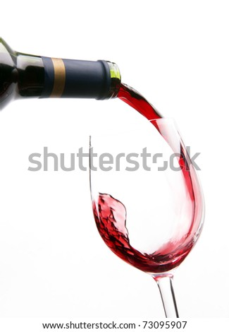 Red Burgundy Wine Pouring into Stemmed Glass Forming a the Shape of Letter J