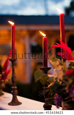 red burning candles and red feathers - stock photo