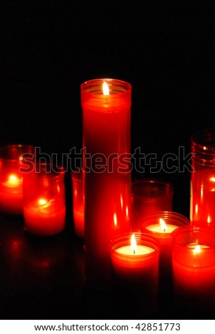 red burning candles in a temple  church  on a black background - stock photo