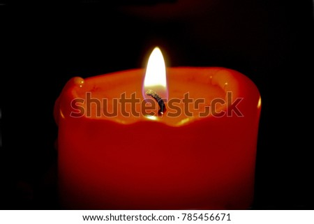 red burning wax candle on a dark background