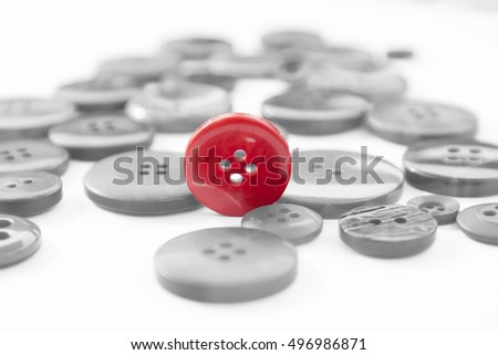 Red button standing on edge among several scattered gray buttons