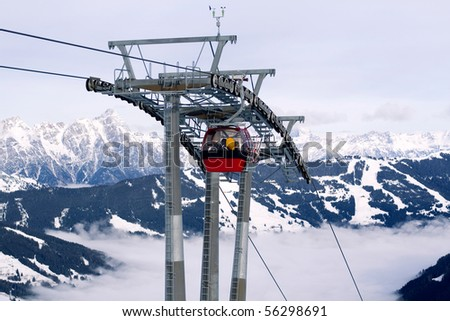 Red cabins of cable-way against white glacier and black mountains