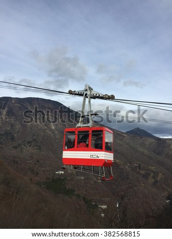 Red cable car with tourists is traveling up to the top of the mountain, Nikko, Japan.  Japanese text at the side of the cable car is written 'Kegon', which is the name of the destination (Kegon Fall)