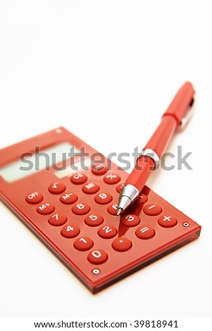 Red calculator and red pen. Close up