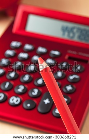Red calculator, red pencil in foreground - stock photo