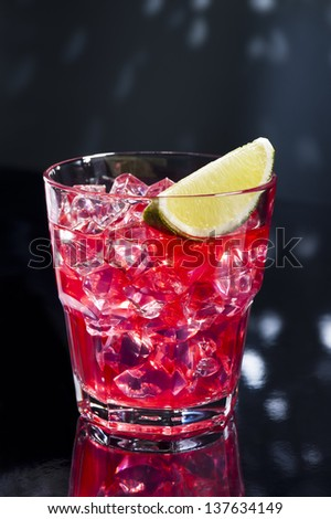 Red Campari Cocktail in short glass with lemon decoration - stock photo