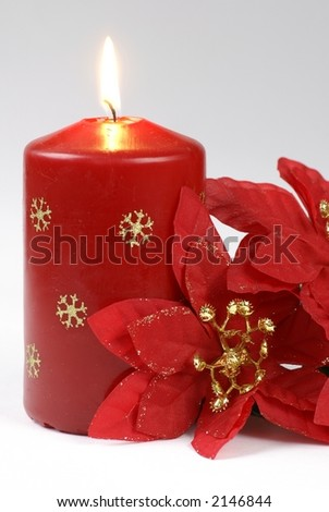 Red candle and poinsettia on white background