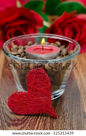 red candle in a glass cup with coffee beans and decorative heart for Valentine's Day