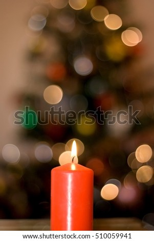 Red candle in front of Christmas tree. Selective focus.