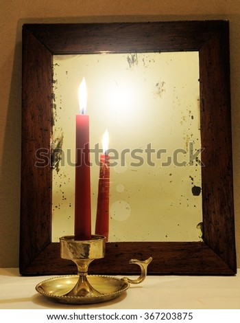 Red candle reflected in old mirror - stock photo