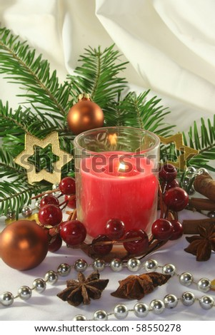 red candle with Christmas ball, stars and pine branches on a light fabric - stock photo
