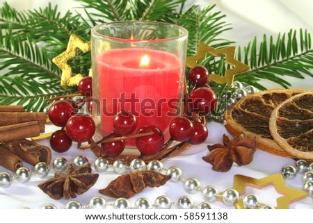 red candle with Christmas ball, stars and pine branches on a light fabric