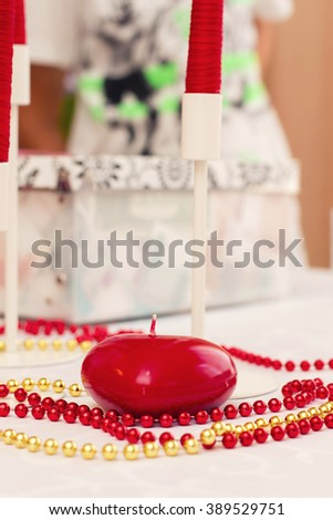 Red Candle with Red and gold Beads on holiday table