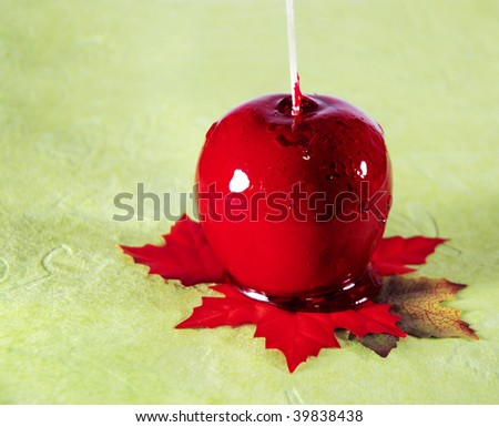 Red candy apple on leaves.Photo can be used during the Autumn and Thanksgiving Seasons. Suggested uses would be greeting card, bulletin cover, banner, poster, print, calendar. - stock photo