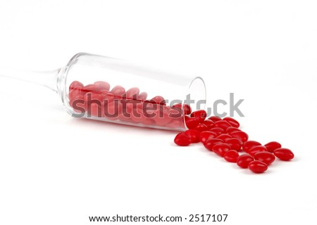 Red candy hearts spilling from a champagne flute.