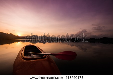 Red canoe boat on the lake with beautiful sunset scene - stock photo