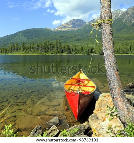 Red canoe moored on the bank of the mountain lake. Jasper National Park, Alberta, Canada - stock photo