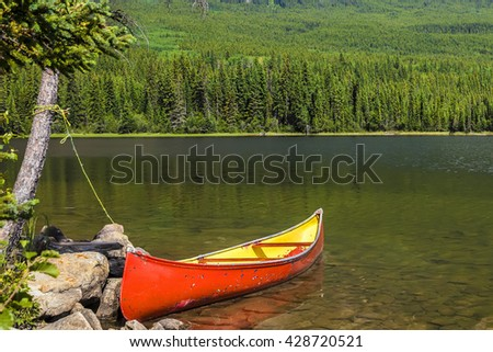 Red canoe moored on the mountain lake. Rocky mountains.Jasper National Park, Alberta, Canada