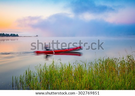 Red canoe on a lake at sunrise - stock photo