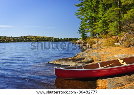 Red canoe on rocky shore of Lake of Two Rivers, Ontario, Canada - stock photo