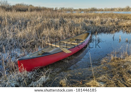 red canoe with a wooden paddle in a wetland, early spring