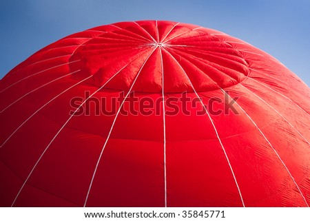 Red canopy of hot air balloon being inflated against a bright blue sky - stock photo