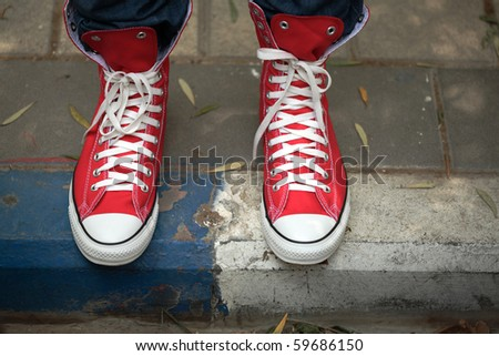 Red canvas sneakers on sidewalk - stock photo