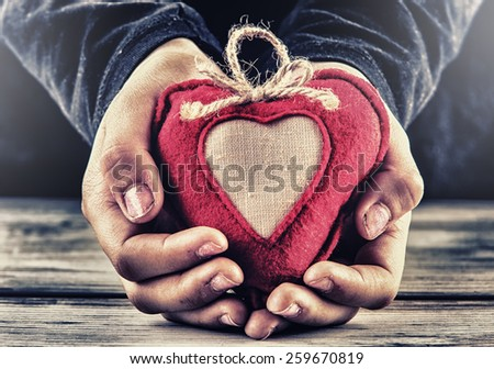Red canvas valentine heart in the hands of a child. Heart gift as a token of love. Colored HDR in the social atmosphere. - stock photo