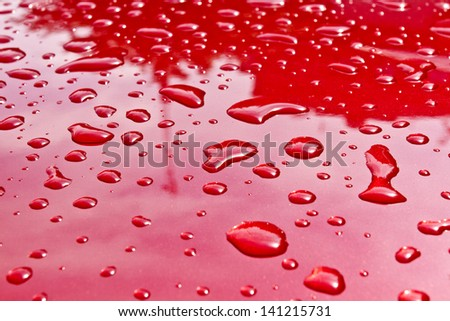 Red car after rain. Water drops collect on top of metal surface/Water drops - stock photo