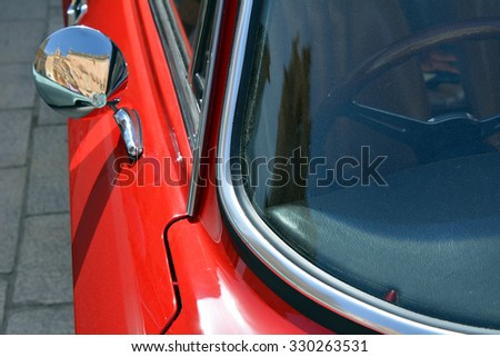 Red car close up with glass and mirror. - stock photo