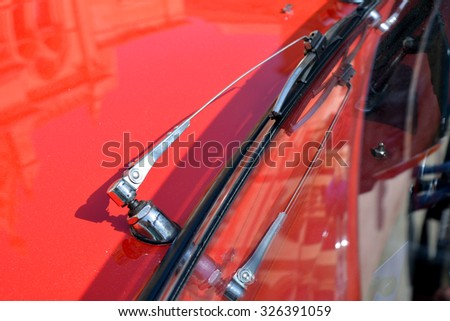 Red car close up with window wiper. - stock photo