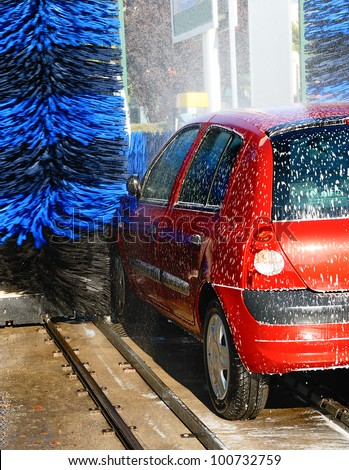 red car during washing process - stock photo
