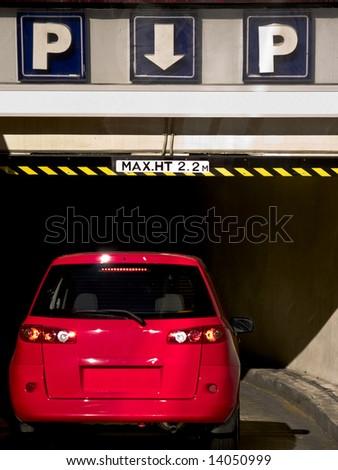 Red car entering underground parking garage - stock photo