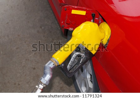 Red car filling up at a gas station - stock photo