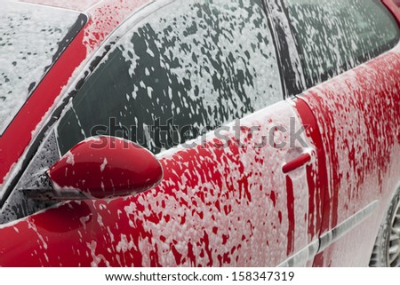 red car getting a wash with soap - stock photo