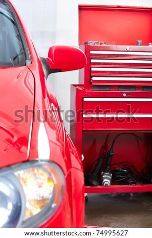 Red car in auto repair shop. Repair. - stock photo