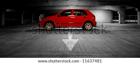 Red car in multi-story parking lot parked by an arrow - stock photo